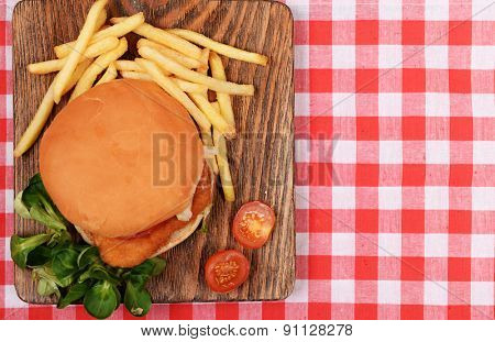 Hamburger, french fries and tomato on table top view