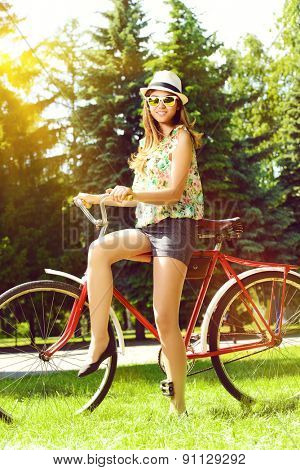 Romantic young woman  with beautiful smile rides a bicycle in a park. Summer day.