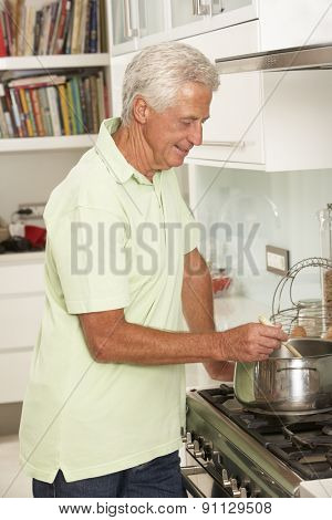 Senior Man Preparing Meal At Cooker