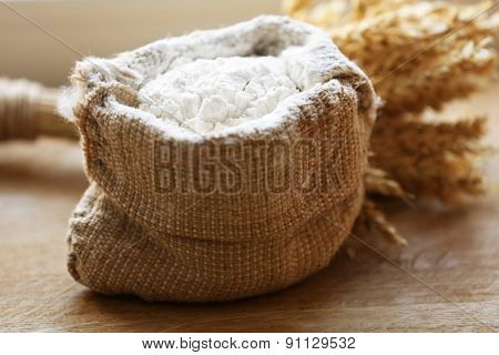 Flour in burlap bag on wooden background