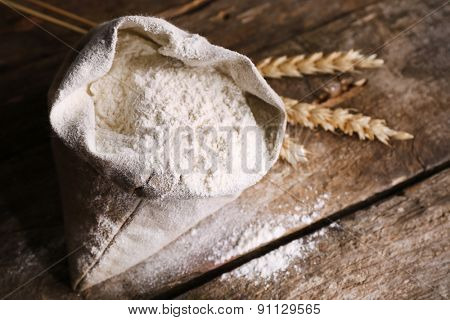 Bag of white flour with wheat ears on wooden background