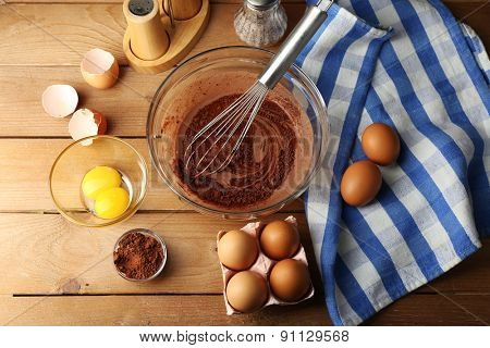 Preparation cream with eggs and cocoa in glass bowl on wooden background