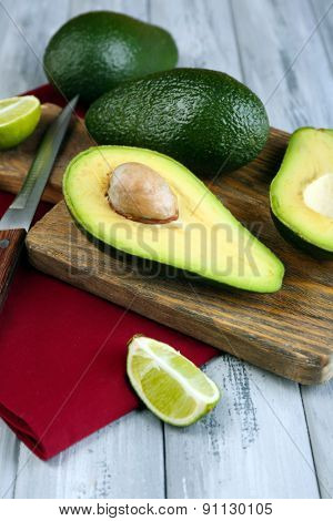 Avocado with limes and  knife on cutting board on table close up