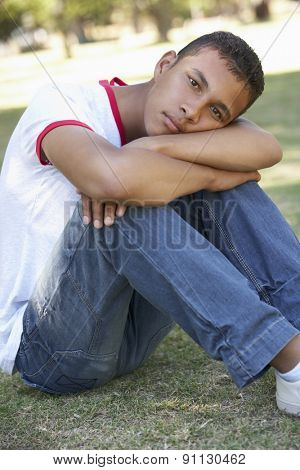 Male College Student Sitting In Park Looking Unhappy