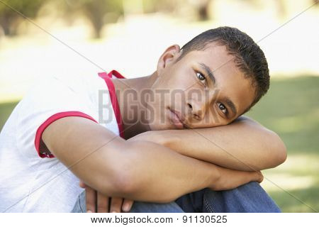 Unhappy Teenage Boy Sitting In Park