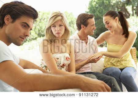 Couple With Problems Amongst Group Of Friends Relaxing On Sofa