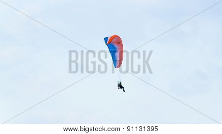 Paraglider flying over a blue sky