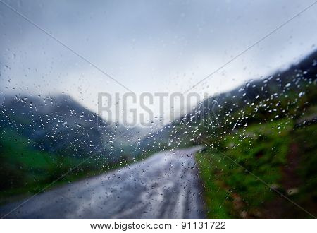 rainy day, car and the road in the rain through the window abstract image