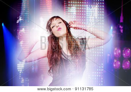 beautiful woman listening to music and singing in concert. LED stage lights. live music