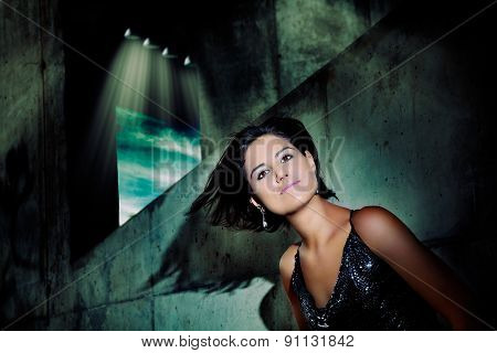 Portrait of beautiful young woman with hair in the wind and city lights background