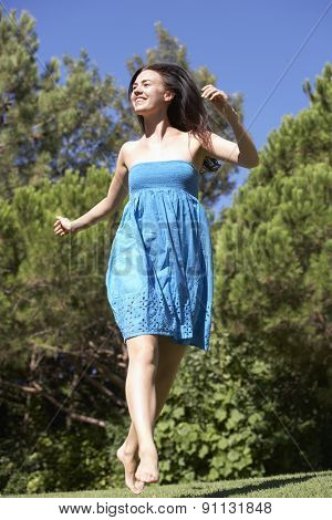 Young Woman Running Through Summer Field