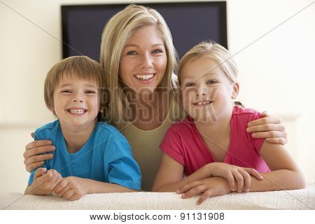 Mother And Children Watching Widescreen TV At Home