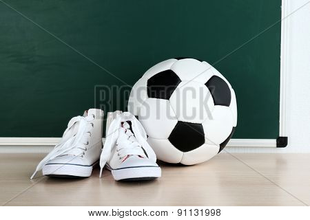 Sport shoes and soccer ball on blackboard background
