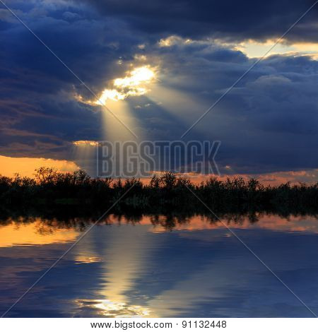 Dark clouds with sun rays over lake water