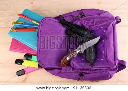 Gun in school backpack on wooden background