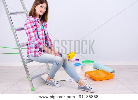 Beautiful girl sitting on ladder with equipment for painting wall