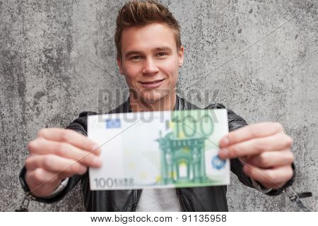 Casual young guy holding 100 euro note