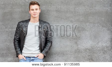 Casual young guy in front of concrete wall
