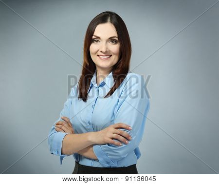 Beautiful middle aged businesswoman on grey background