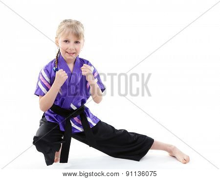 Little girl in kimono doing exercises isolated on white