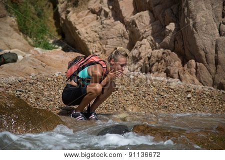 Adventure Girl Wash Her Face In The Wild River.