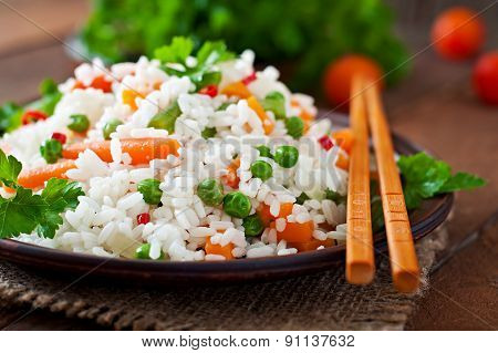 Appetizing healthy rice with vegetables in a ceramic dish on a wooden background. Selective focus.