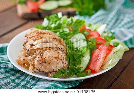 Baked chicken breast and fresh vegetables on the plate on a wooden background