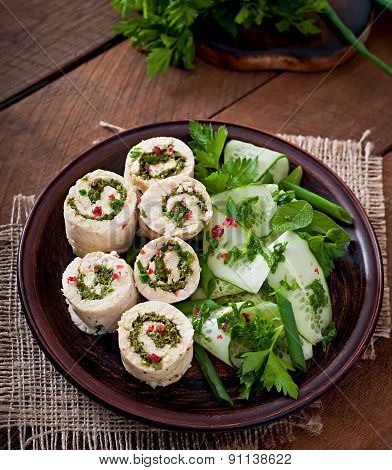 Steamed chicken rolls with greens and fresh vegetable salad on a brown plate