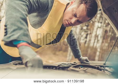 Man fixing broken car on a roadside
