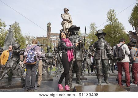 Tourist Poses With Bronze Night Watch By Rembrandt On Square In Amsterdam