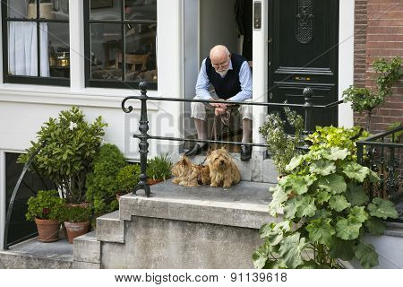 Elderly Man Sits With Two Dogs In Doorway Of Canal House In Amsterdam