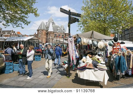 Tourists Reading A Map Near Market Stall On Nieuwmarkt In Amsterdam