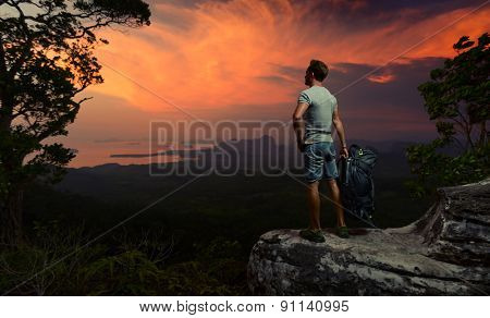 Young hiker standing on the rock and enjoying bright tropical sunset