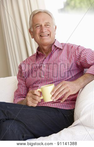 Senior Man Relaxing At Home With Hot Drink