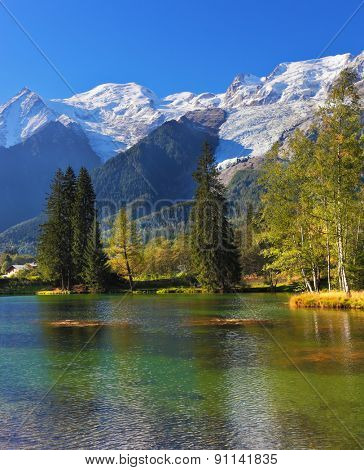 Cozy urban park in Chamonix, Provence. Snowy Alps picturesquely surrounded by evergreen trees and lake