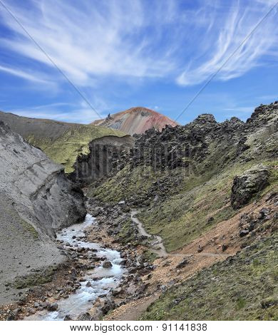 Creek at the bottom of a picturesque gorge and the path down the mountainside. National Park Landmannalaugar in Iceland