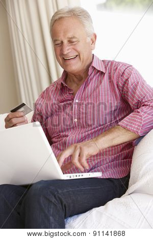 Senior Man Using Laptop For Online Purchase At Home