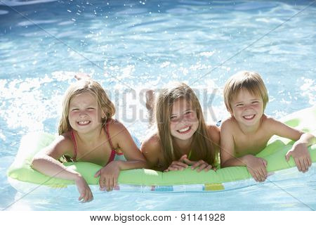 Group Of Children Relaxing In Swimming Pool Together