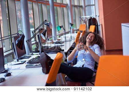 happy young curly  business woman in the modern office have coffee break and relaxing