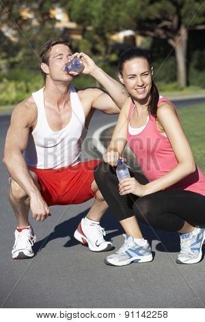 Young Couple Resting And Drinking Water After Exercise