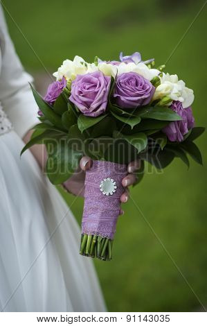 Bridal Bouquet Of Purple And White Roses In Bride's Hands