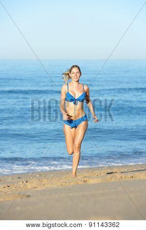 Young Woman Running Along Summer Beach