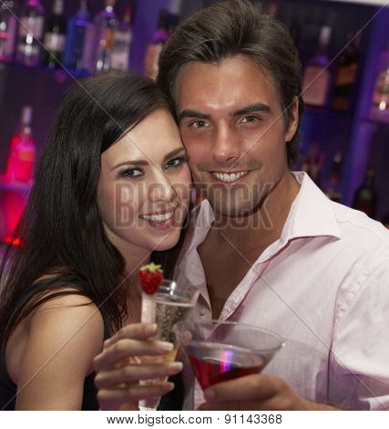Young Couple Enjoying Drinks In Bar