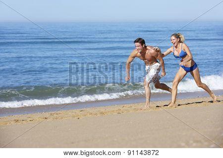 Young Couple Running Along Summer Beach