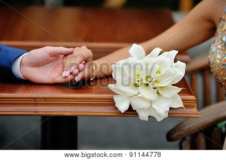 Wedding Bouquet Of Calla Lilies On A Background Of The Bride And Groom Hands