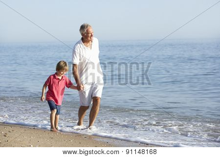 Grandfather And Grandson Enjoying Walk Along Beach