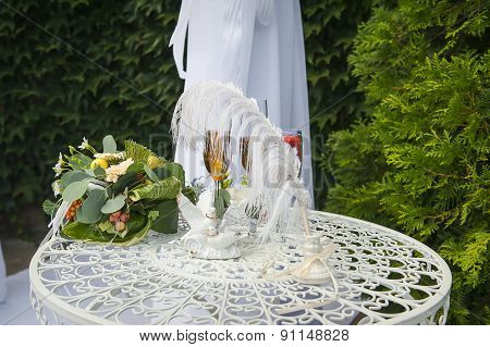 A Wedding Bouquet Is Glasses With Champagne And Rings