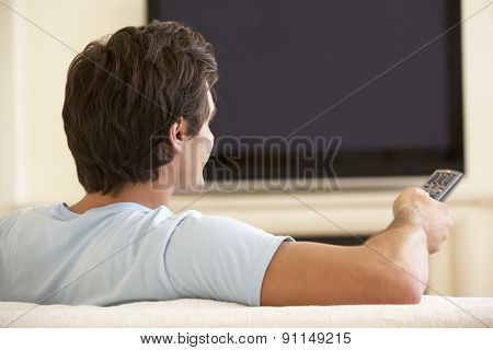 Man Watching Widescreen TV At Home