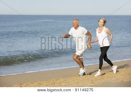 Senior Couple Jogging Along Beach