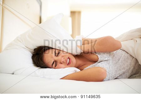 Woman Lying In Bed Covering Ears With Pillow